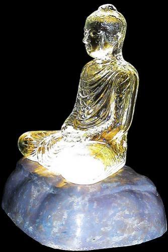 พระแก้วใสปางคันธารราฐทรงพระหัตถ์สมาธิ ประทับบนฐานโลหะทรงก้อนหิน ภายในฐานมีแสงไฟส่องผ่านองค์พระออกมา